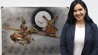 Stephanie Macias Arlington standing in front of a painting in a office
