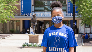 Student on Campus in Front of the Rec Center Wearing a Mask