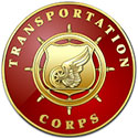 The Transportation Corps seal is a red circle with a golden shield containing a car wheel with a wing on it all in front of a ship's steering wheel.