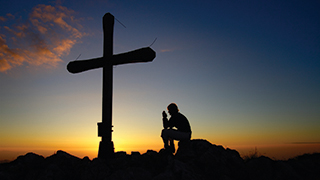 Man Praying by a Cross at Sunset