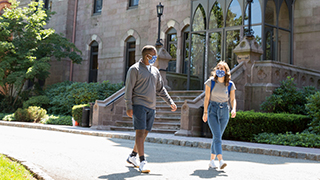 Two students wearing masks walking on campus in front of Presidents Hall.