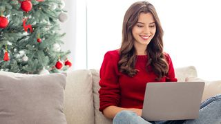Woman sitting on couch with laptop during Christmas