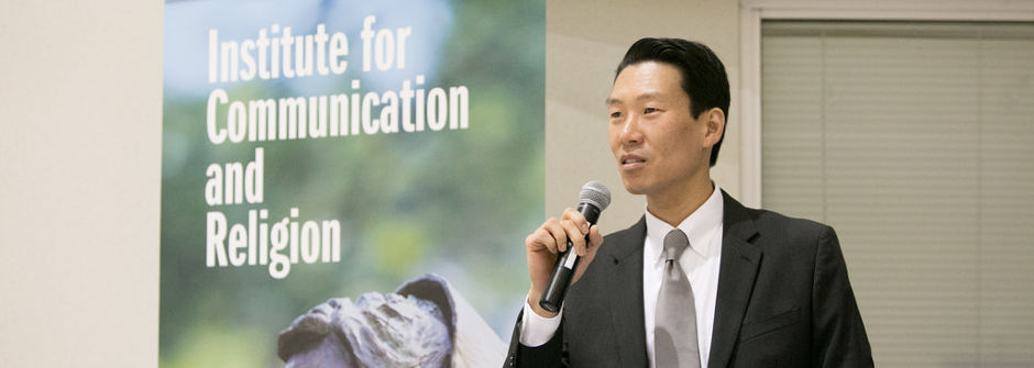 Ki Joo Choi speaking with a microphone at the inaugural event for the Institute of Communication and Religion.