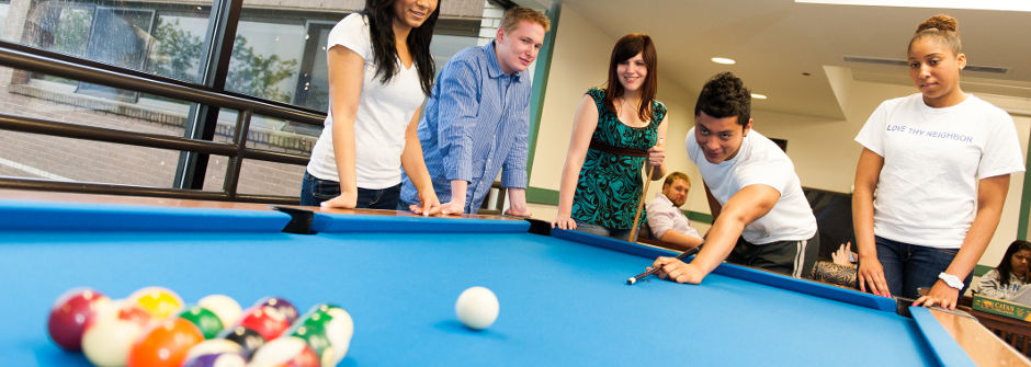 Students playing pool in Xavier Hall.