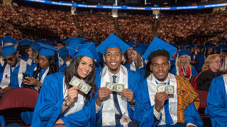 Graduates holding up one dollar bills at the Commencement Ceremony.