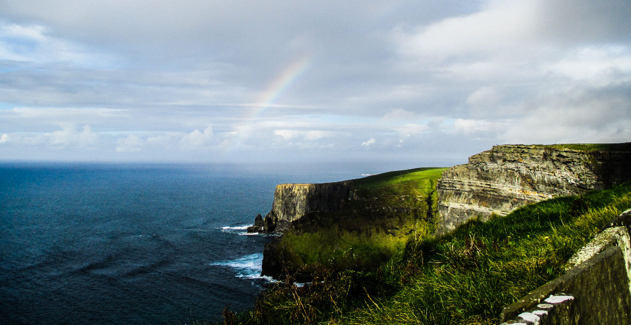 Cliffs in Ireland looking out at a rainbow at sea.