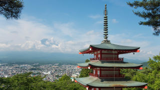 Japanese temple over looking town and mountain.