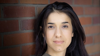 Nadia Murad in front of a brick wall.