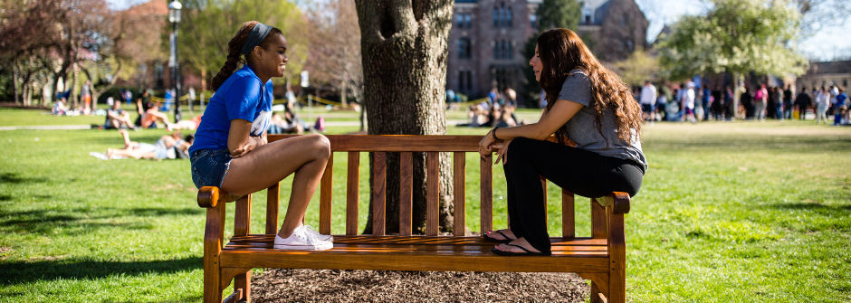 Students talking one-on-one on a bench