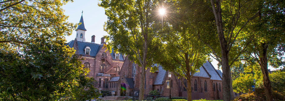 An image of President's Hall and the sun shining through trees above the chapel.