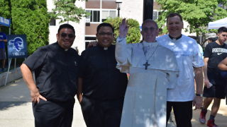 Priests on incoming freshman Move-in-Day with a cut-out of Pope Francis.