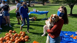 Student with Dog at Fall Pumpkin Event