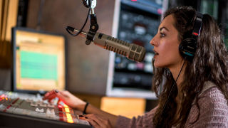 A student broadcasting on a microphone and sound board at WSOU.