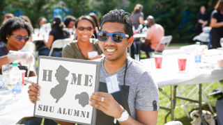 "Alum holding a stencil that reads ""Home SHU Alumni"" with a cut out of the state of New Jersey."