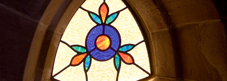 Stained glass window with sun shining through.