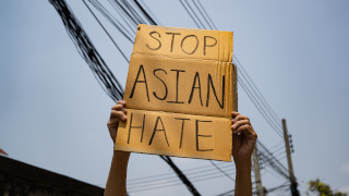 A person holding a Stop Asian Hate cardboard cut out sign.