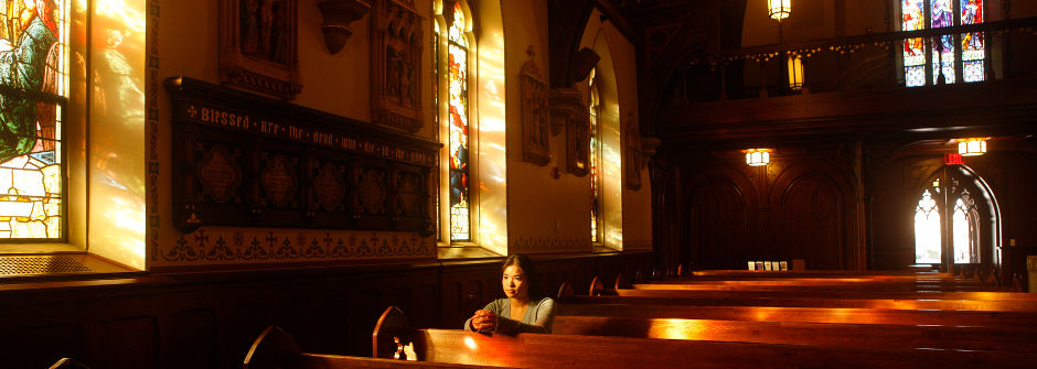 Student in a pew in the chapel.