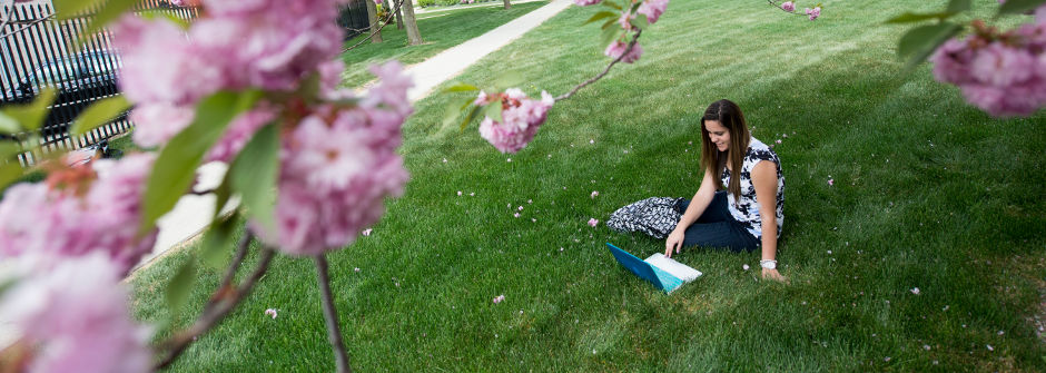 Student on laptop sitting on the grass.