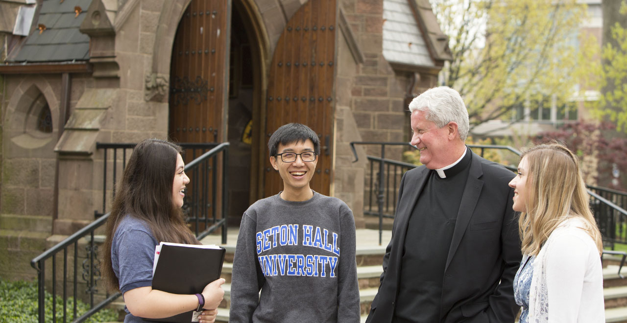 Priest on campus with students