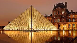 Photo of the Louvre Pyramid in France at night.