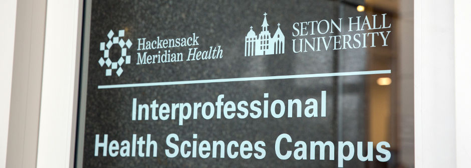 "IHS Door sign with the Hackensack Meridian Health and the Seton Hall logos above the words ""Interprofessional Health Sciences Campus."""