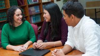 Three students from the Unanue Institute talking to each other while sitting at a table.