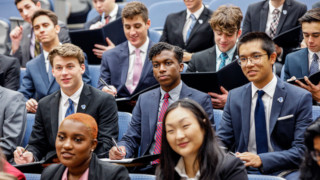 Student listening in a lecture hall in suits.