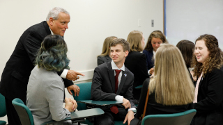 Group of students sitting around at desks in a classroom listening to a speaker all dressed in business attire.