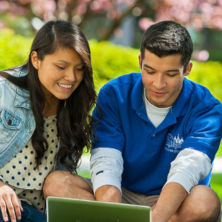 Two students using a laptop outside