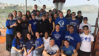 Group photo of Seton Hall students gathered by the Sea of Galilee