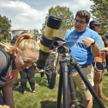 Physics professor Jose Lopez explaining the significance of the solar eclipse to a student looking through a telescope.