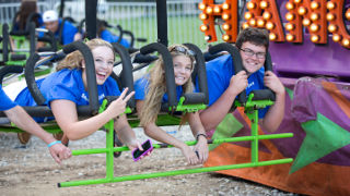 Students laying on their stomachs on a carnival ride.