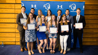 Student athletes holding up certificate awards.