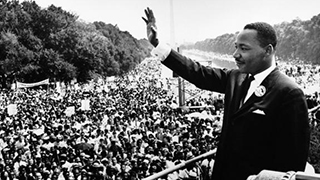 Rev. Dr. Martin Luther King Jr. on the steps of the Lincoln Memorial in Washington D.C. waving to a crowd of people.