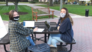 Students at picnic table in masks