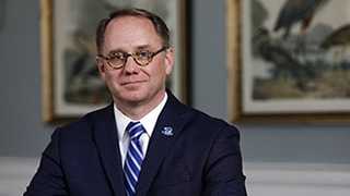 Dr. Jospeh Nyre sitting at desk