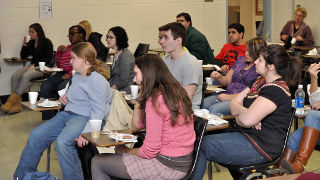 Students sitting at desks and eating food during a Slavic Club meeting.