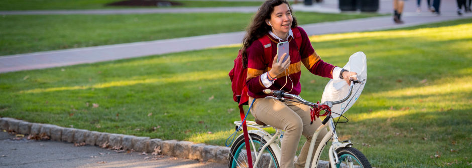 Student on the go with her phone on a bike.