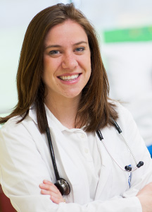 Emily Slate, in her white coat, with a stethoscope.
