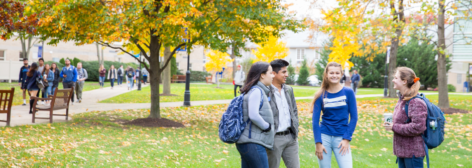 A group of four students talking on campus.